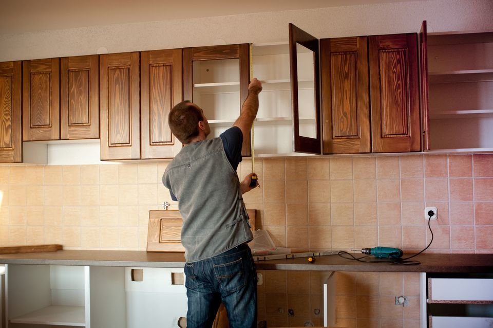 Man constructing cabinet units in a new kitchen