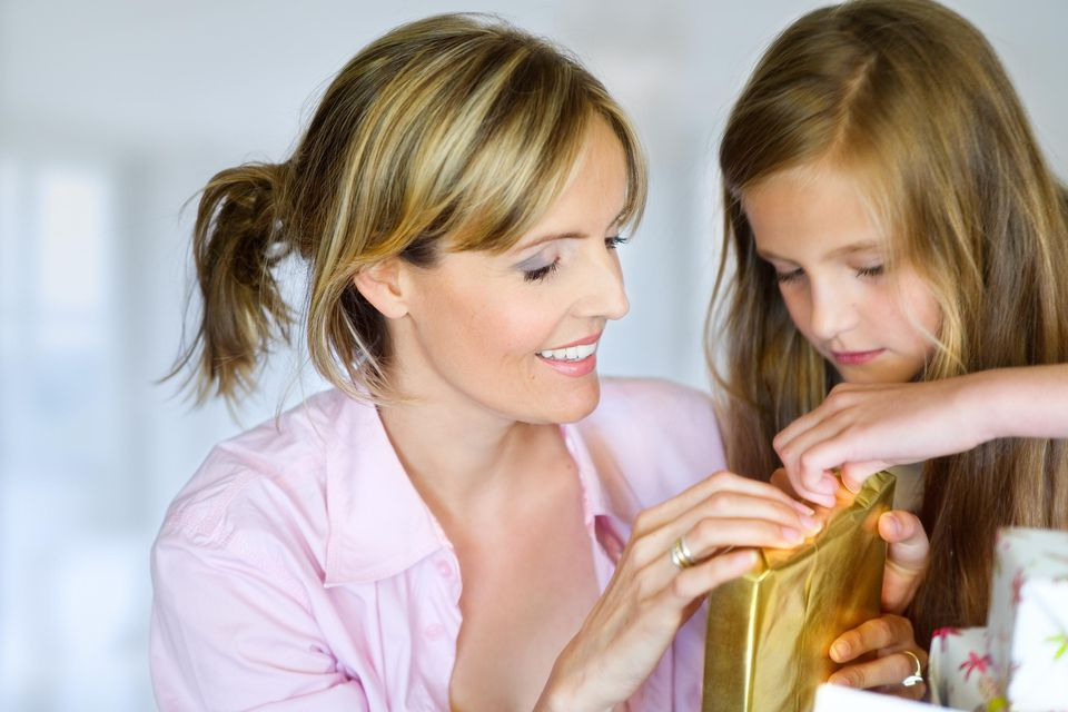 tween girl opening gift with her mother
