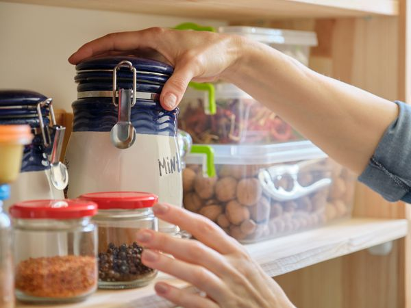 Close up of woman's hands organizing jars on a pantry shelf.