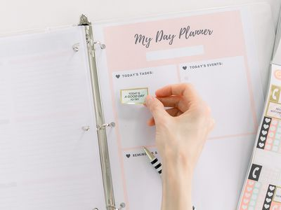 a person placing stickers on a planner page
