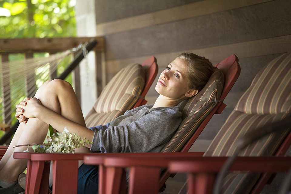 Young Woman Relaxing on Lawn Chair on Porch