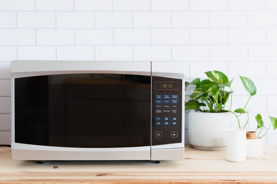 Silver and black microwave oven on wooden counter next to potted plant in white pot