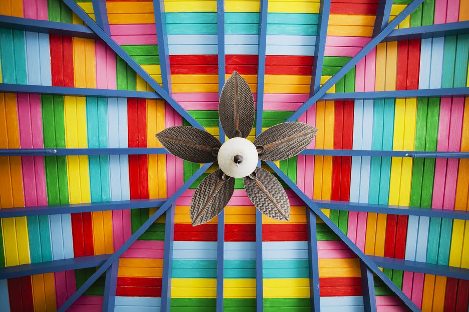 Petal-shaped fan on multi-coloured wooden ceiling