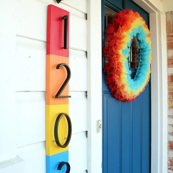 Colorful vertical house number sign next to a blue door.