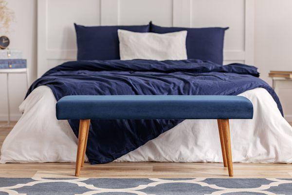 Navy velvet comforter on bed with royal blue velvet footstool