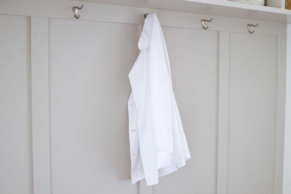 White chef coat hanging on hook