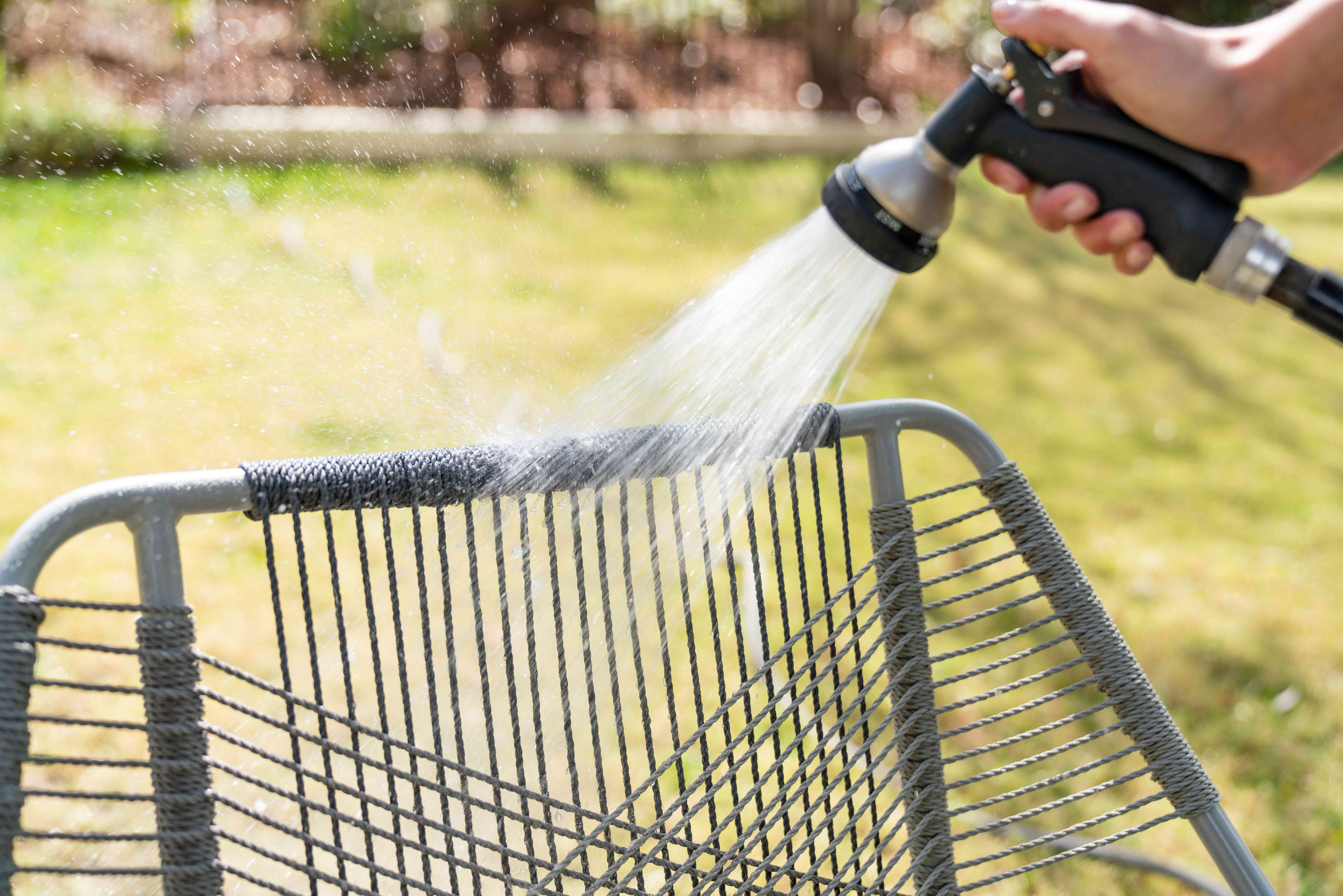 Hose spraying water on outdoor fabric to rinse off bird poop stain