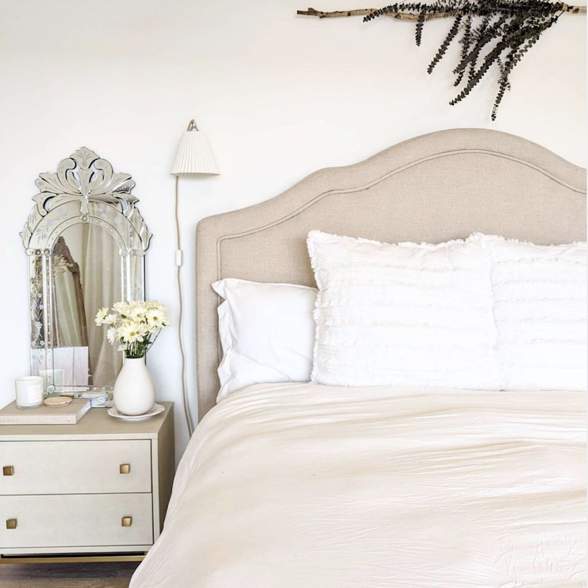 neutral bedroom with silver ornate mirror on bedside table