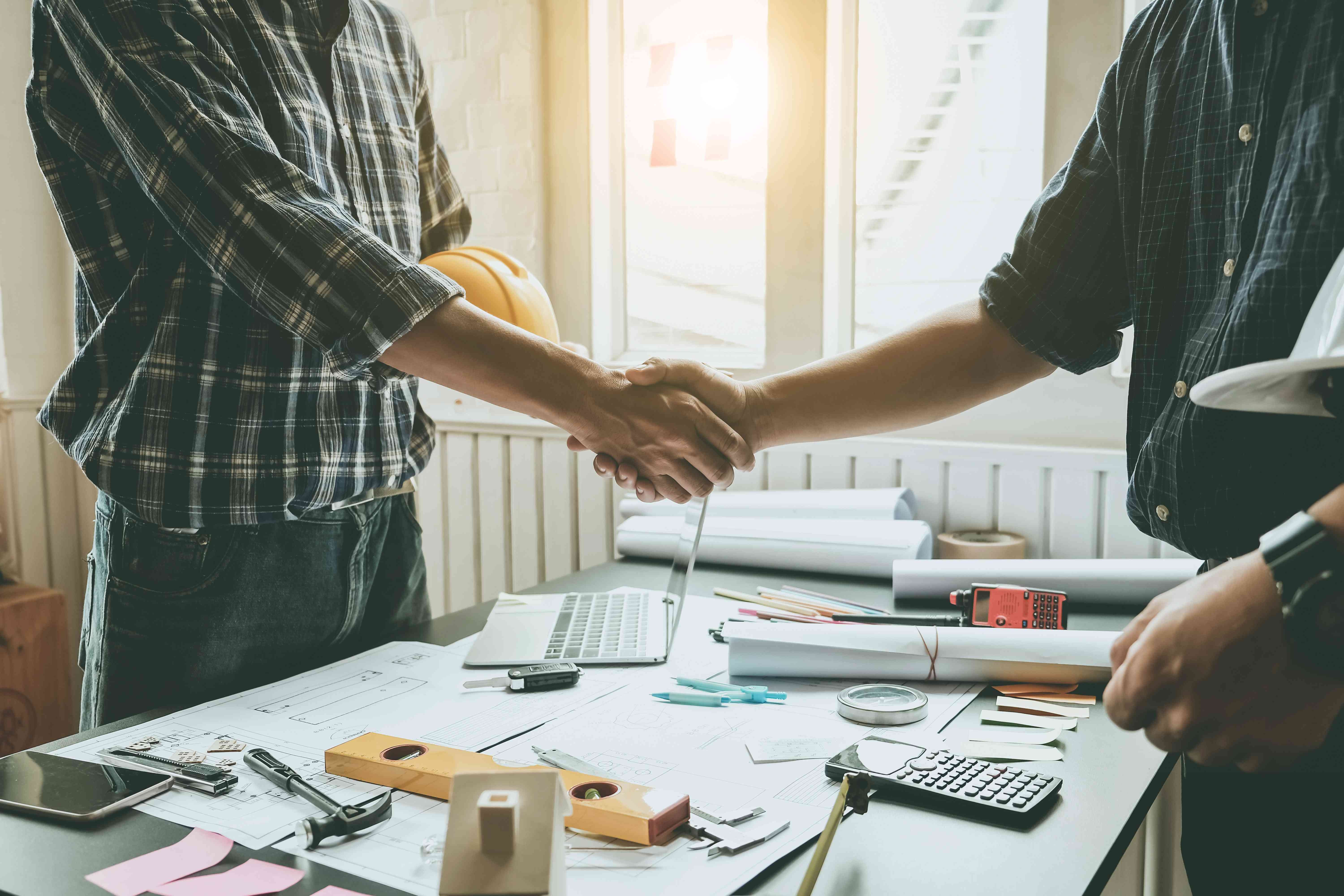 Engineers and architects handshake. Agreement and are willing to work together.