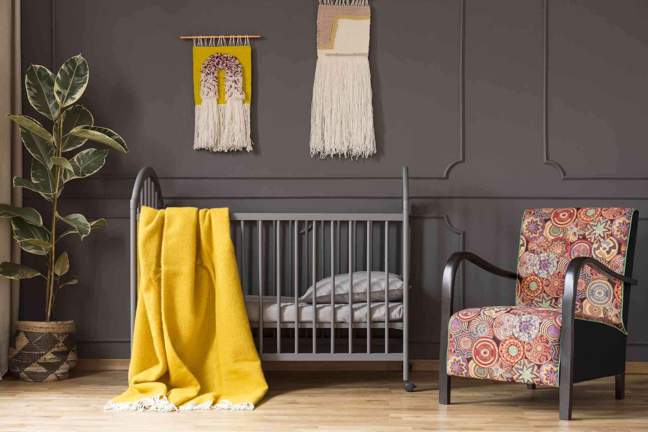 Patterned armchair next to bed with yellow blanket in kid's bedroom interior with ficus. Real photo