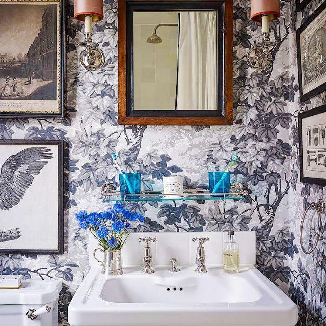 baño con un lavabo de pedestal y papel tapiz retro