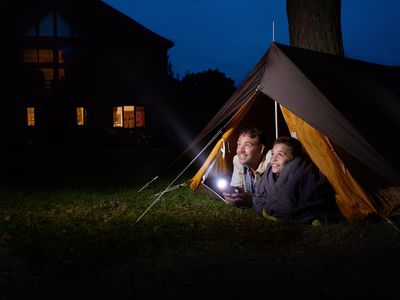 Father and son in tent shining flashlight in distance