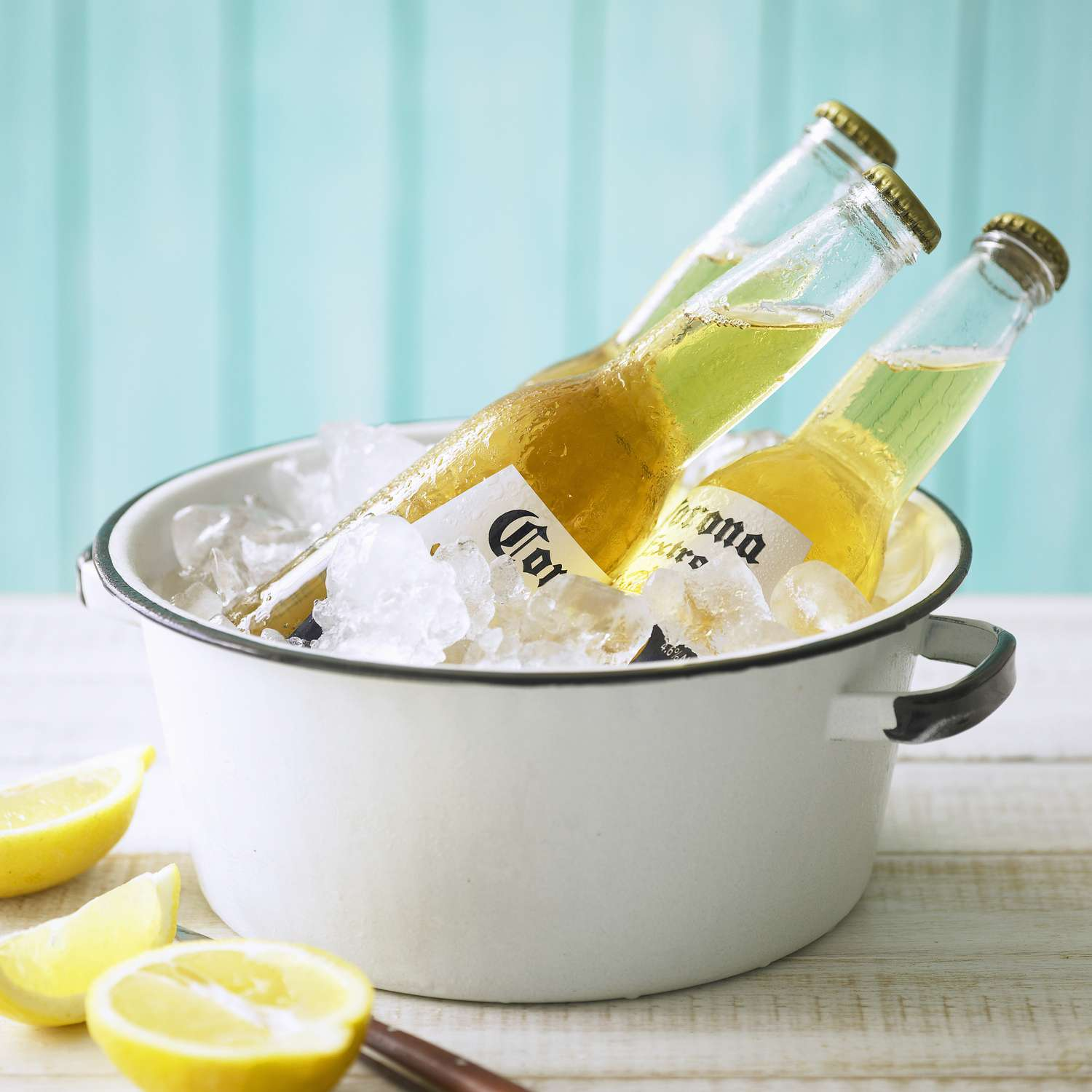 Three bottles of Corona beer in a pot with ice and lemons on the table.