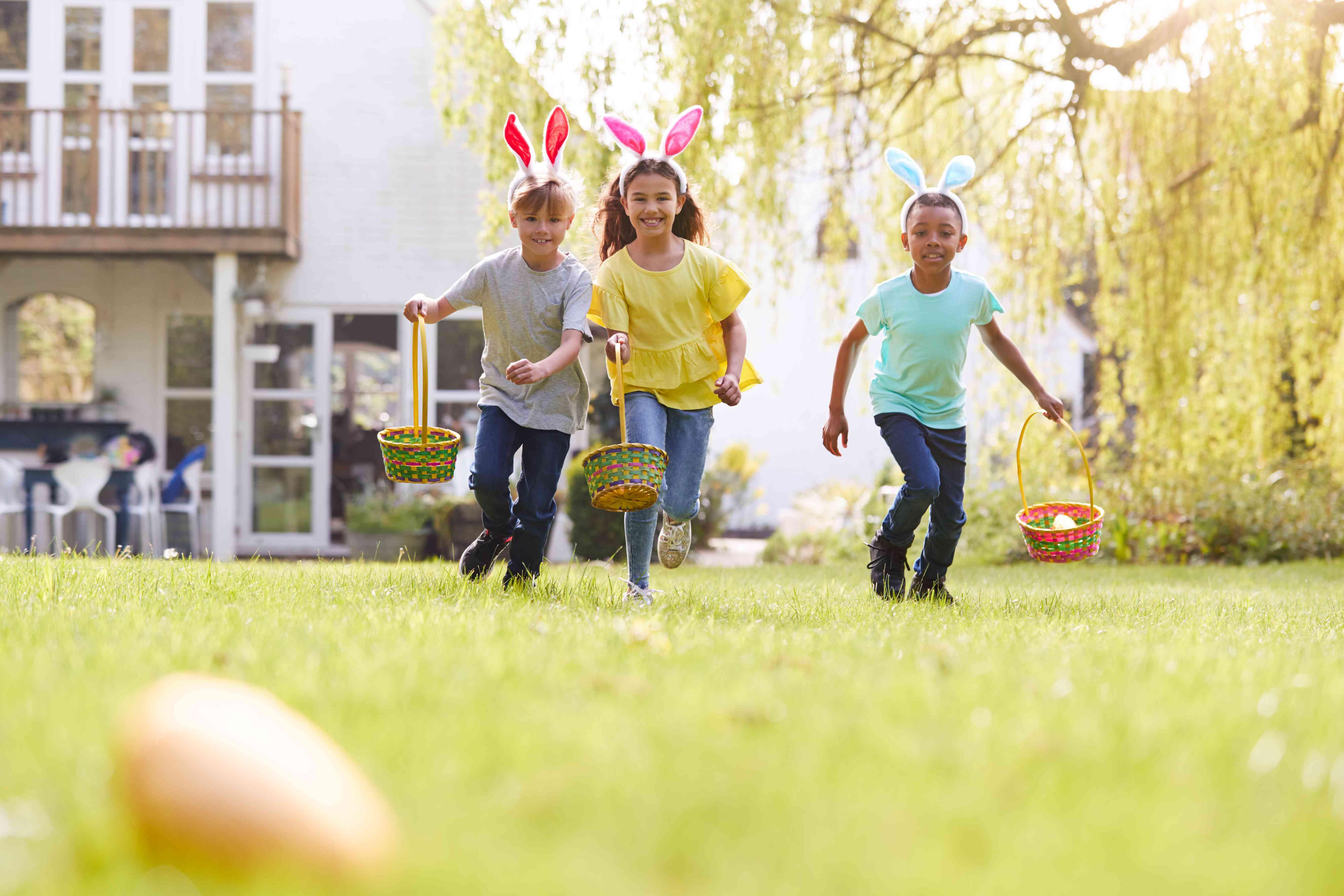 Group Of Children Wearing Bunny Ears Running On Easter Egg Hunt In Garden