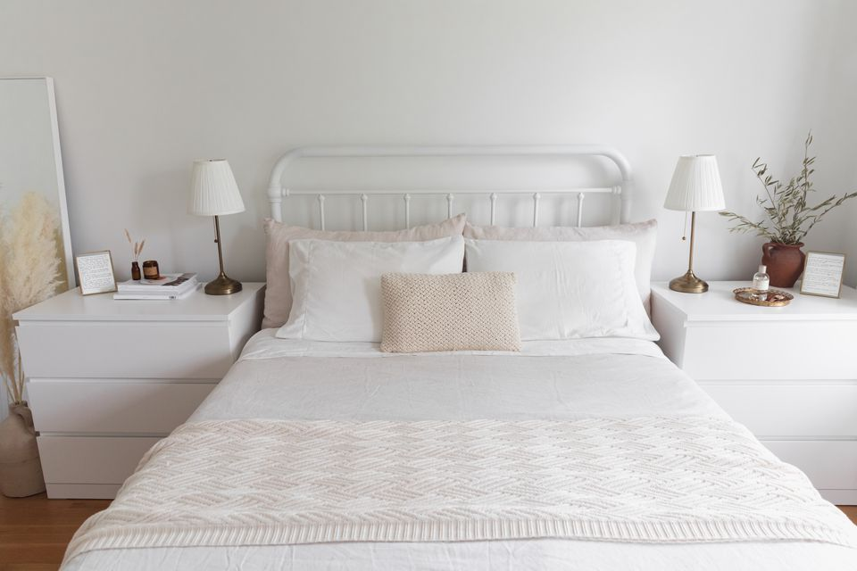 White walled bedroom with white nightstands on either side of bed with white sheets and pillows