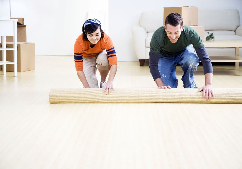 Couple unrolling a carpet after they move in