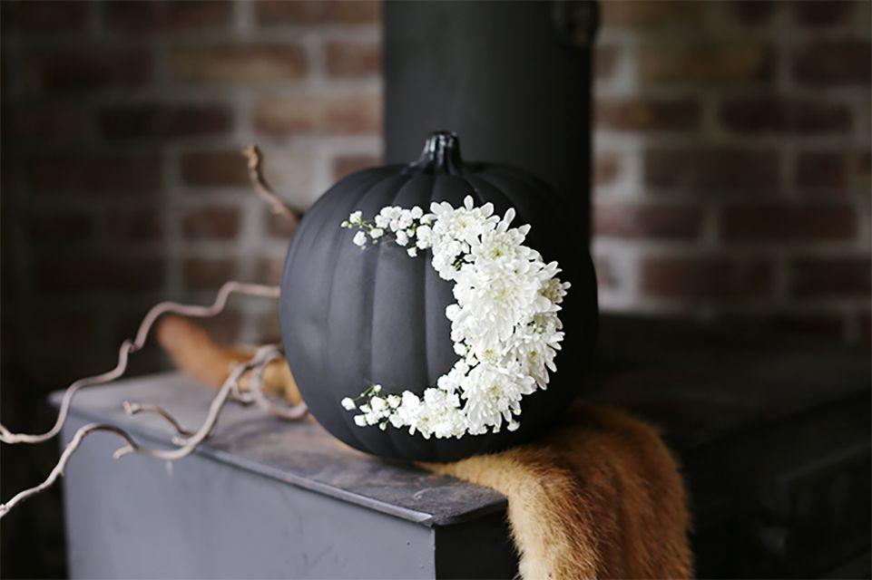 A black pumpkin with a white moon