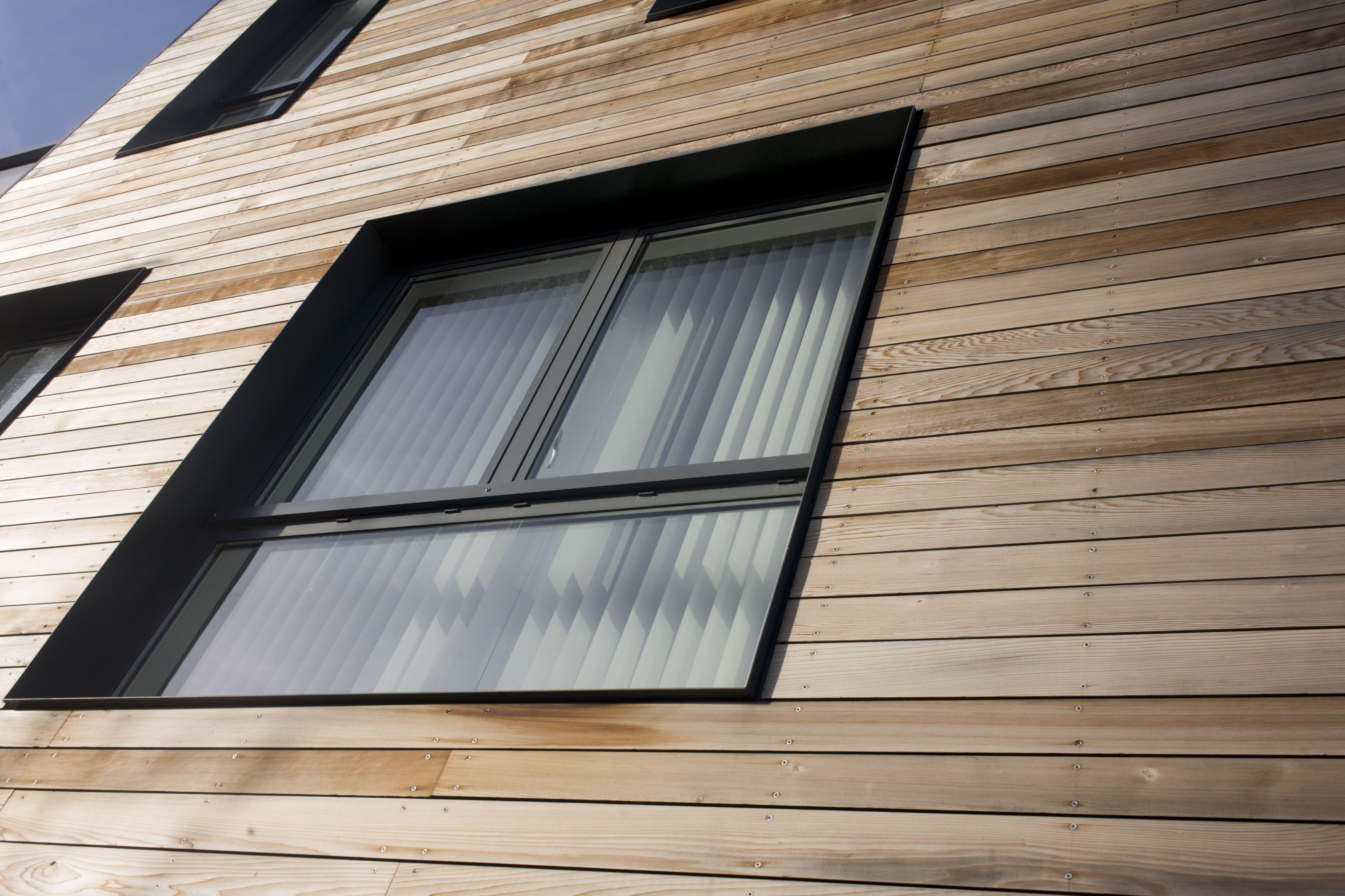 Ventana negra de tres paneles con revestimiento de madera natural