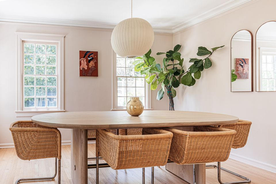 Dining room with walls painted in neutral beige color with oval table and wicker chairs in middle