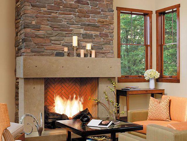 Revestimiento de chimenea de piedra con fuego ardiente y velas en el manto