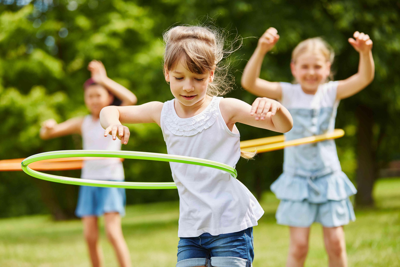 Girls Spinning Plastic Hoops In Park