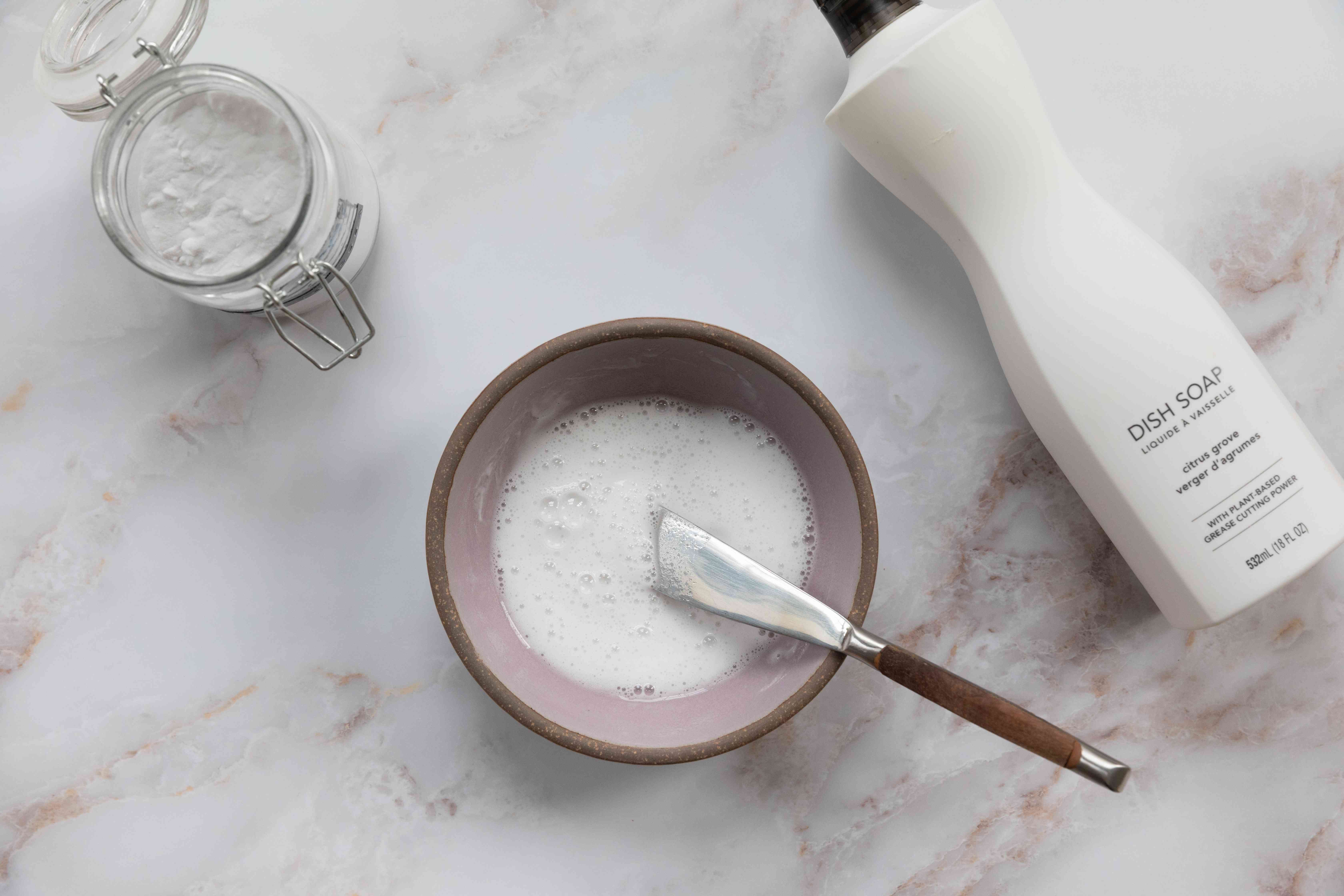 Baking soda and dish soap containers next to bowl of mixed cleaning solution for pink mold