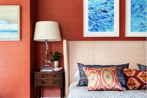 red bedroom with ocean prints over the bed, white pattern headboard, dark wood bedside table