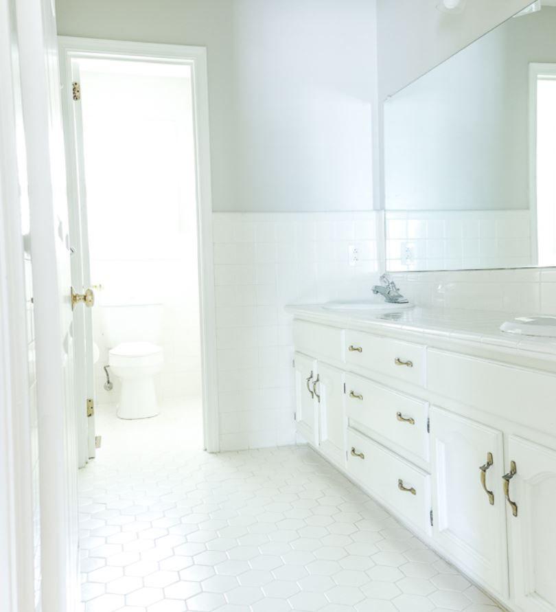All white narrow bathroom.