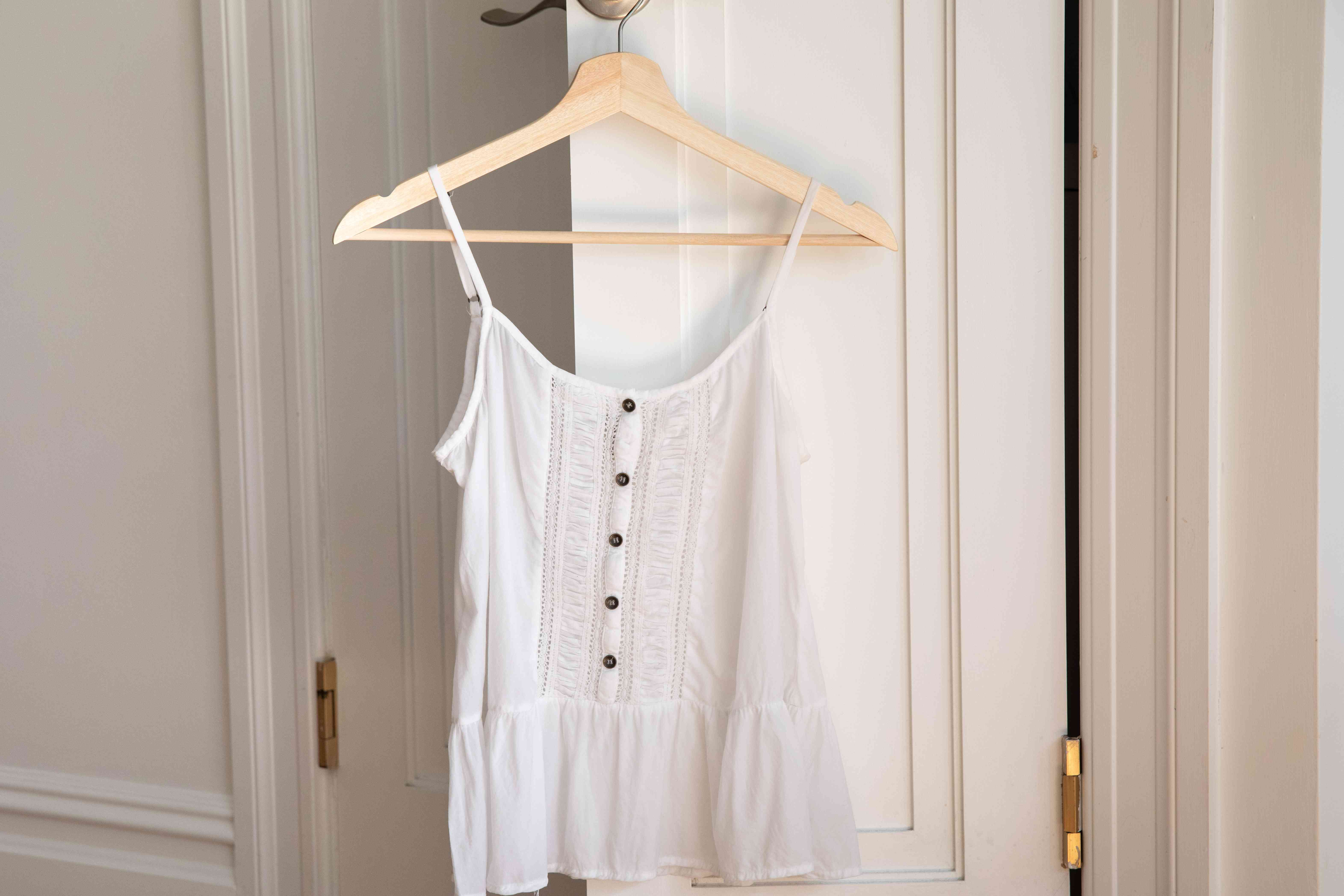 A white rayon top hanging from a hanger