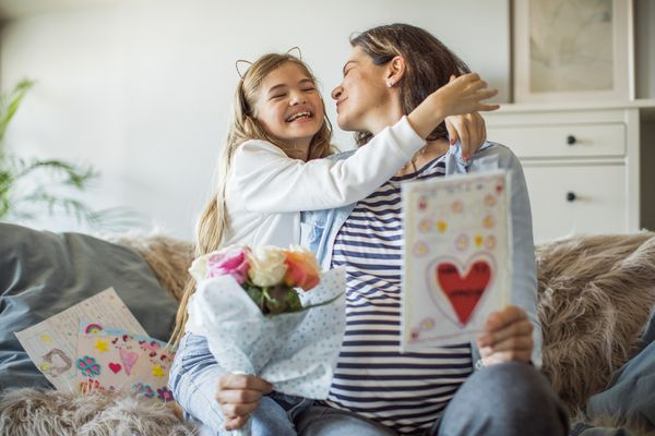 A mom and her daughter together while opening a Mother's Day card.