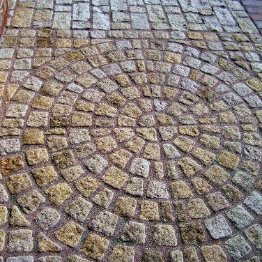 photo of old world-style cobblestones in circle fan pattern