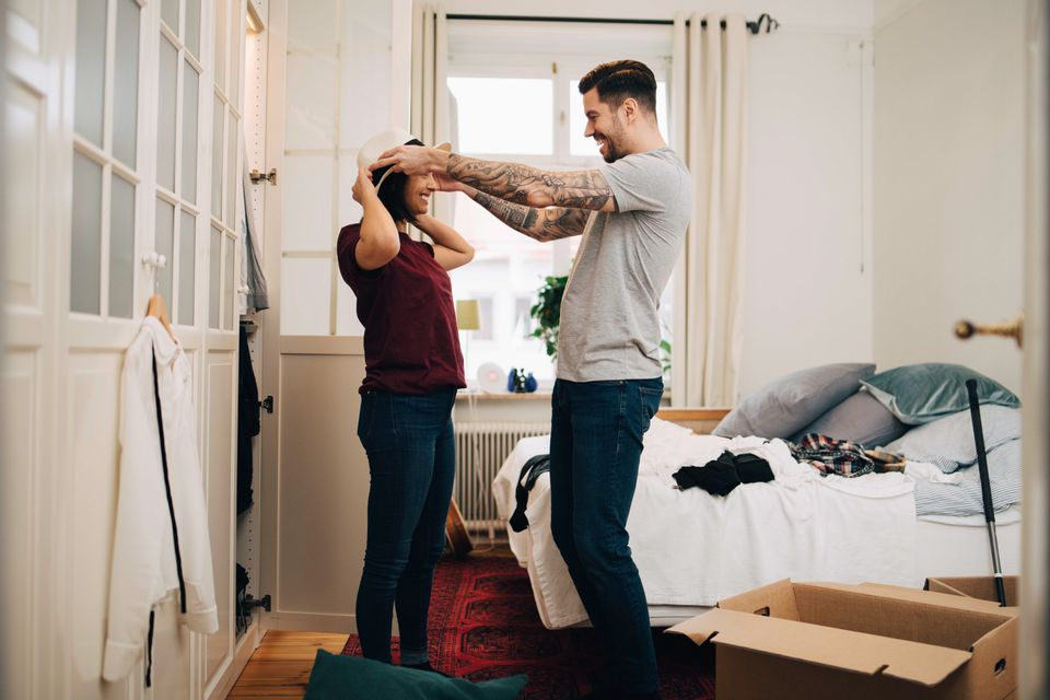Man adjusting hat on woman at bedroom during relocation