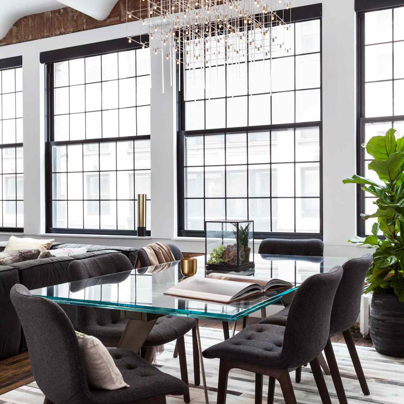 the dining area in this home features white walls and huge windows