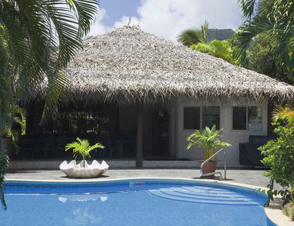 A cabana with a thatched roof near a pool.