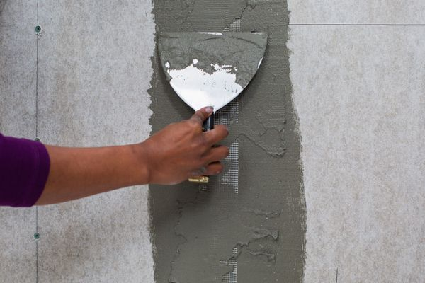 person using cement on a backer board