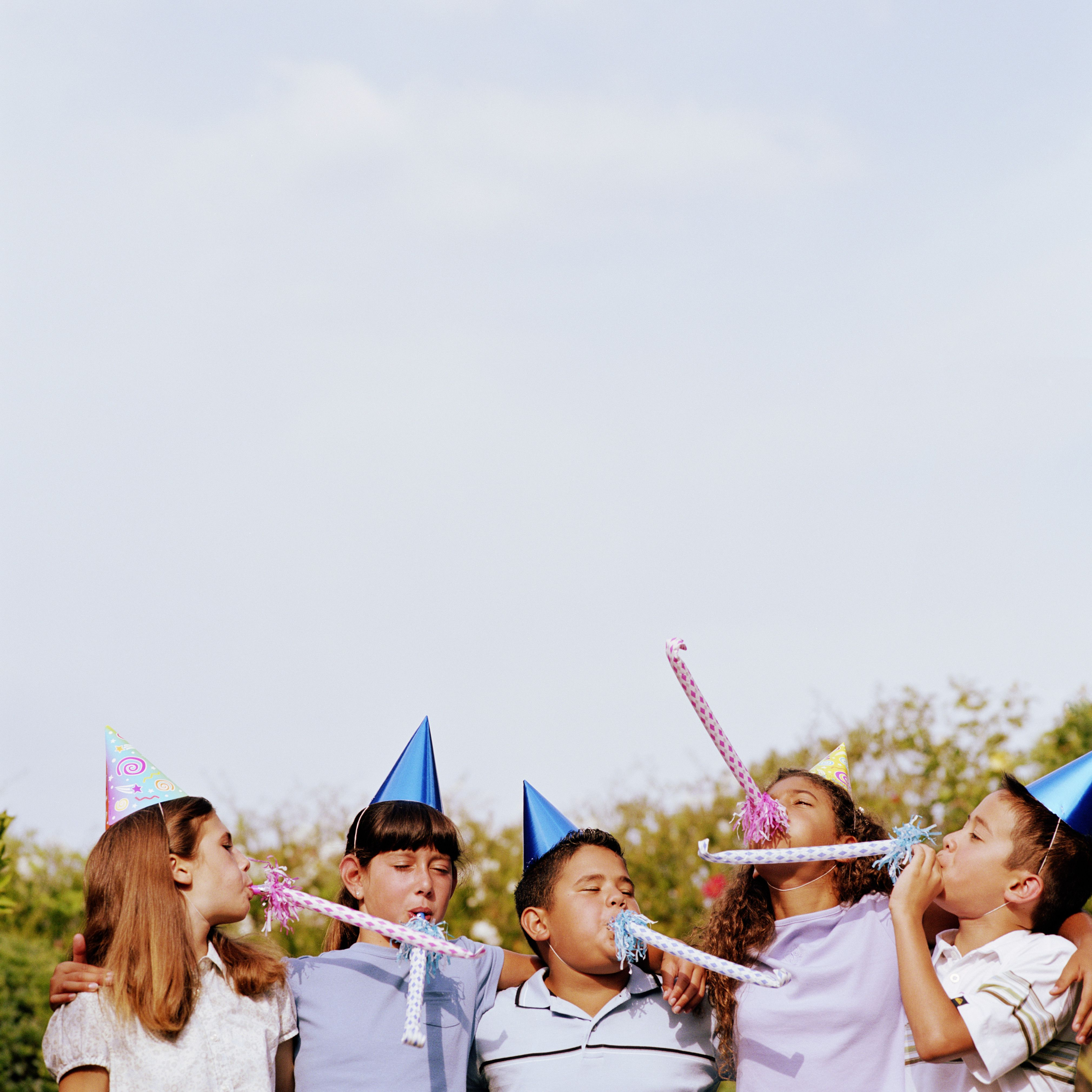 Group of children in party hats blowing party favors, high section