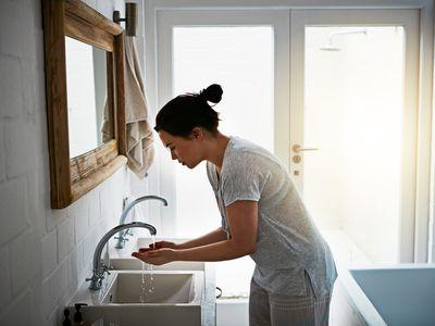 Woman washing hands in bathrrom