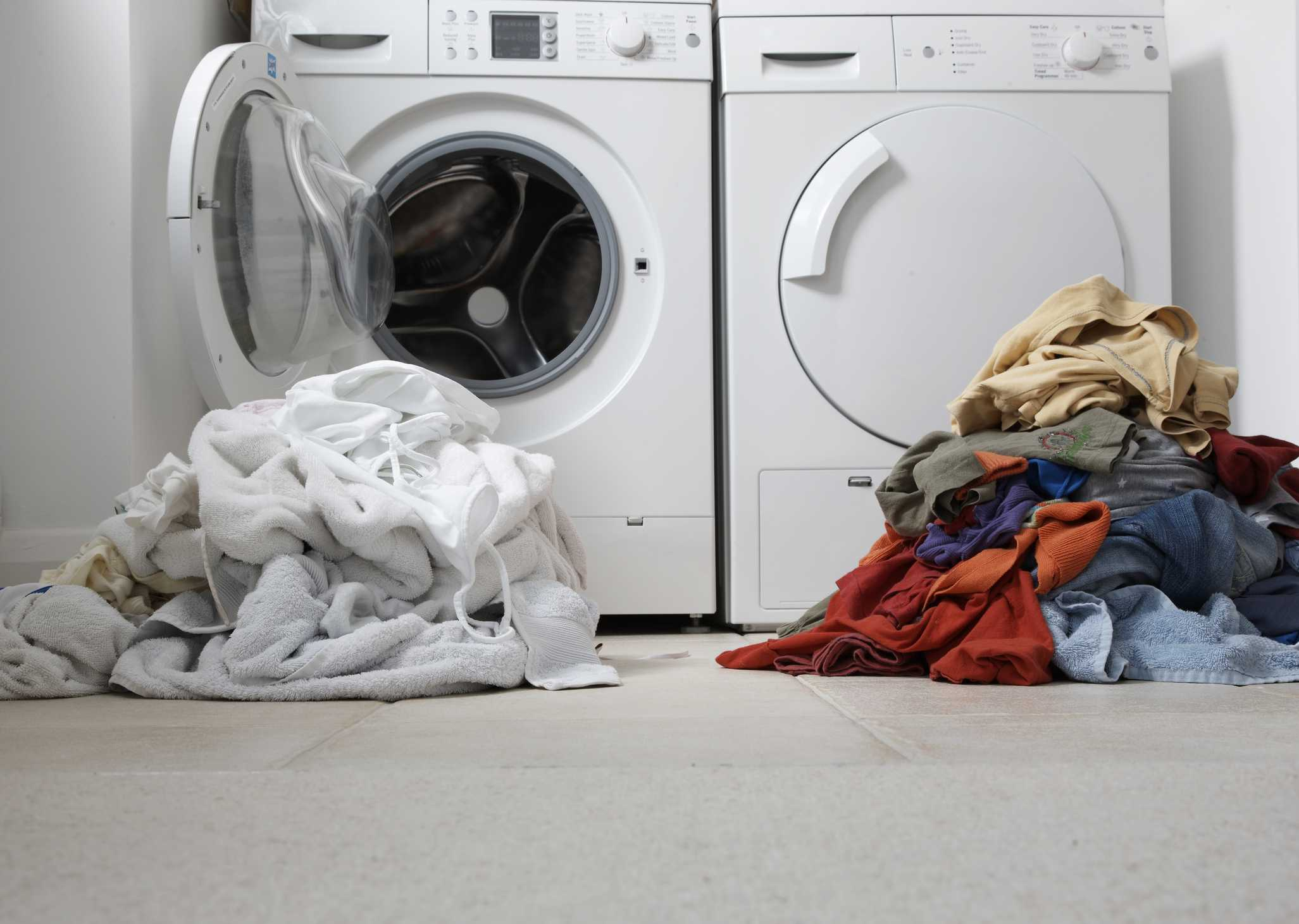 Sorted laundry in front of a washer and dryer