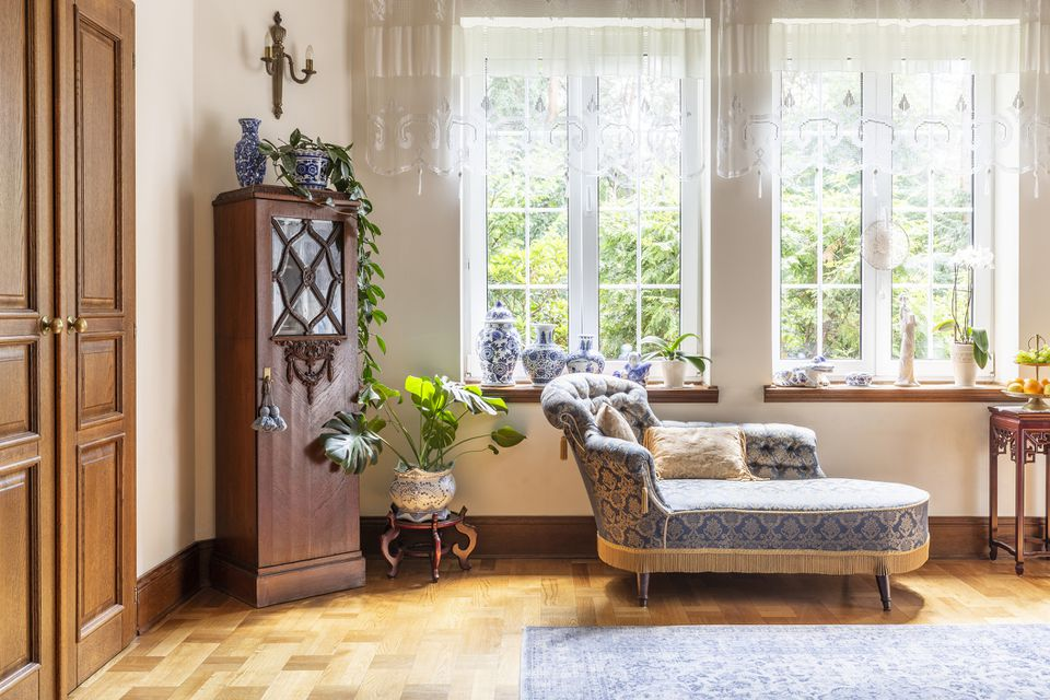 A luxurious living room interior with a couch and a wooden cabinet standing on a parquet against two large windows. Real photo.