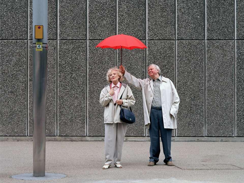 Senior hombre sosteniendo paraguas rojo sobre mujer, de pie sobre el pavimento
