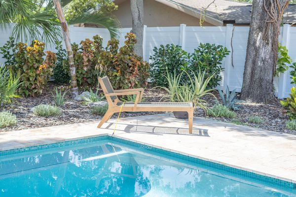 Pool furniture attached to pool corner with landscape in the back