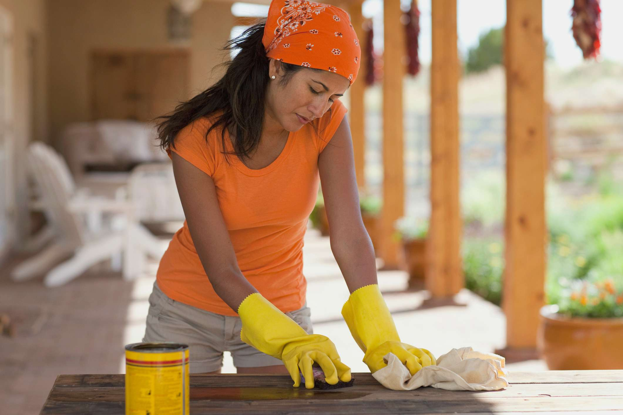 woman oiling outdoor furniture