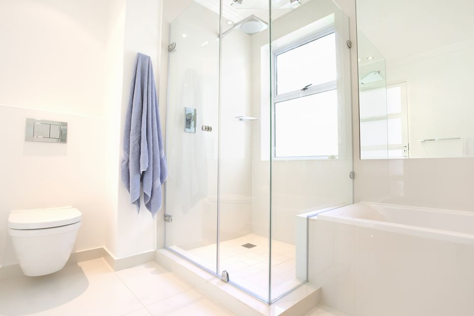 Stand-up shower unit next to bathtub and toilet, all white.