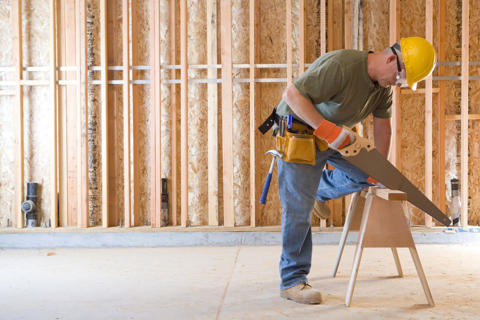 Builder in a hardhat sawing a board