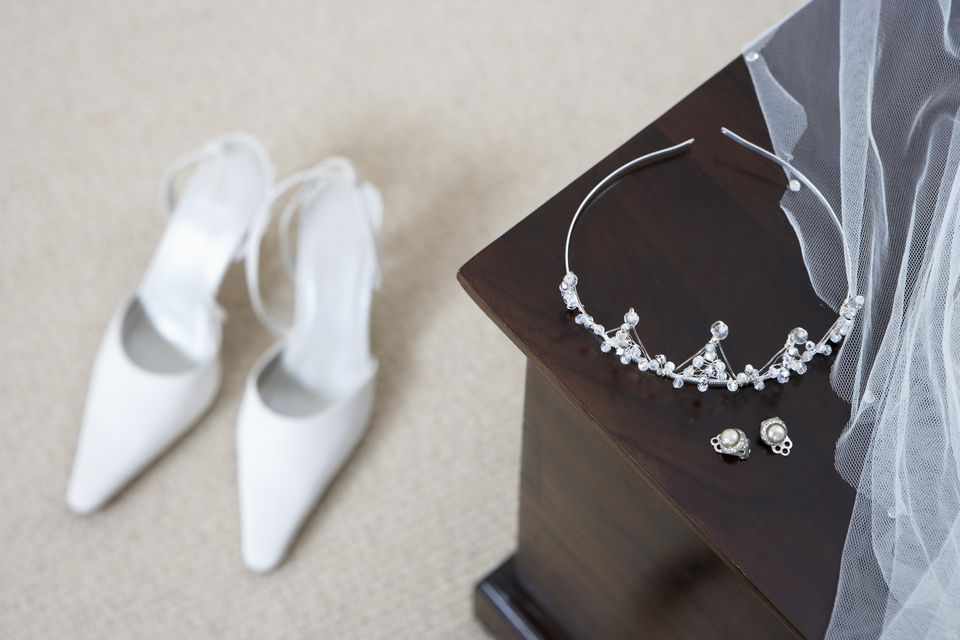Tiara and earrings on a cabinet, shoes on floor