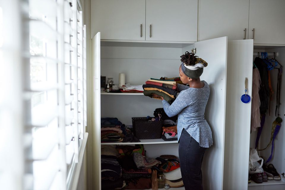 A woman putting folded clothes into a closet