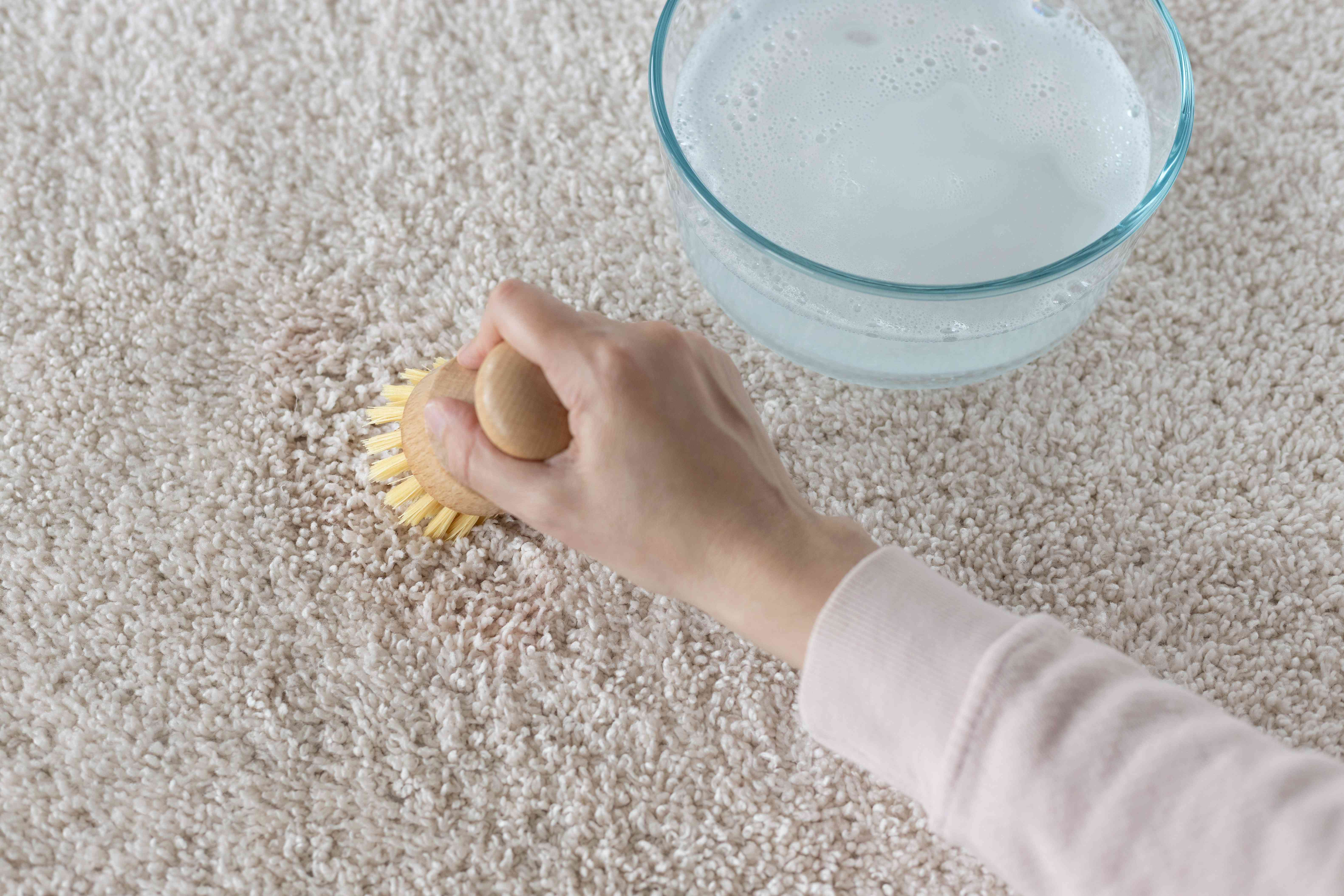 Soft-bristled brush scrubbing fruit punch stain with oxygen-based bleach and water solution on carpet