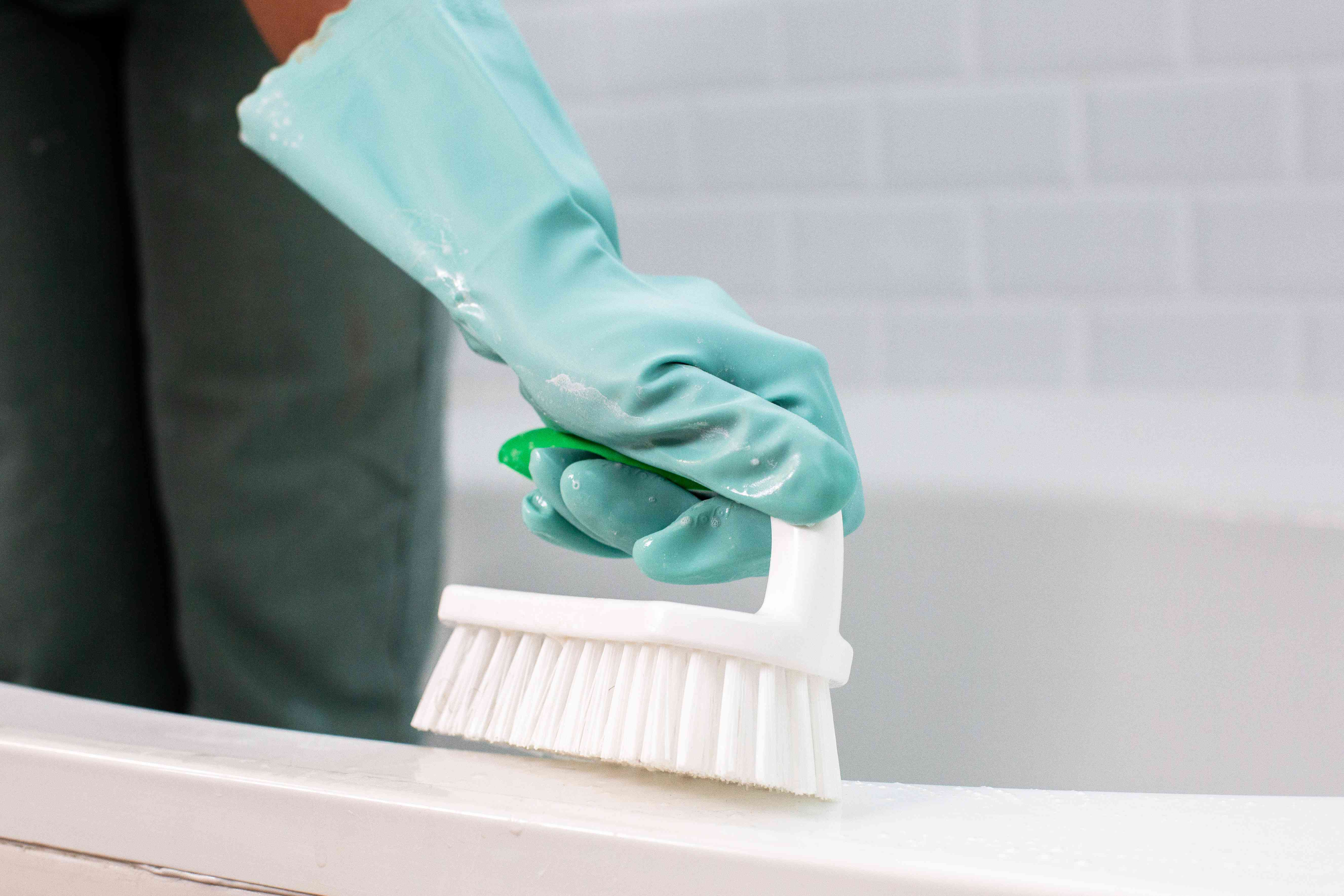 Bathtub cleaned with scrubbing brush and teal rubber gloves