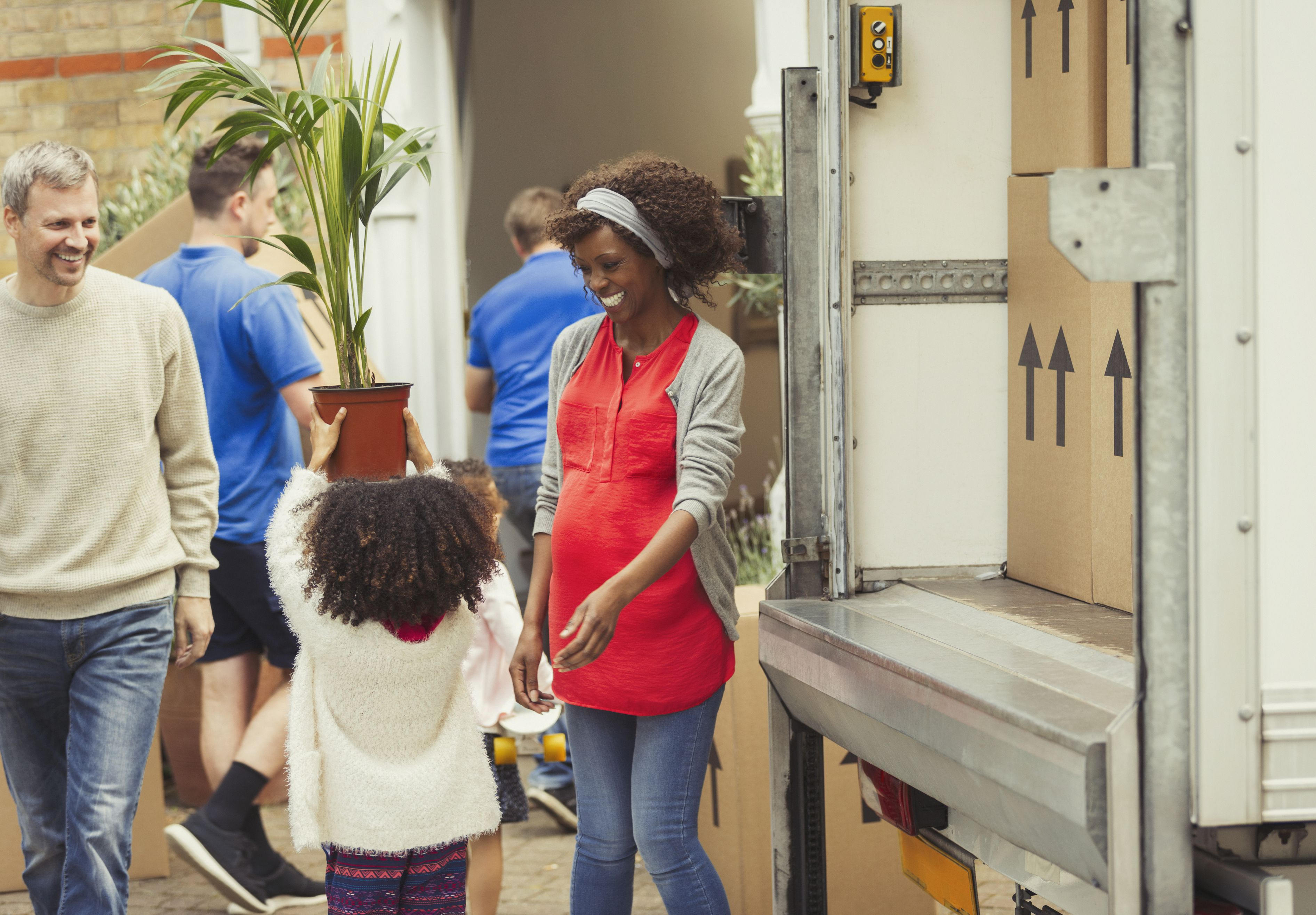 Multi-ethnic young family unloading moving van outside new house