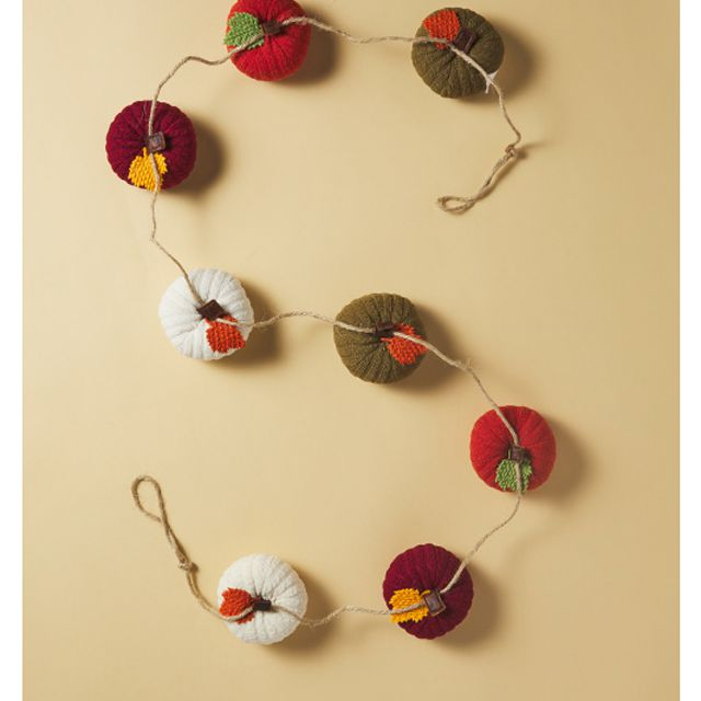 A garland with multicolored knitted pumpkins